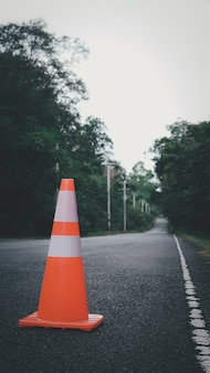 Cono di traffico arancione viene utilizzato per avvertire di non entrare in auto sulla strada di campagna in thailandia. Foto Premium