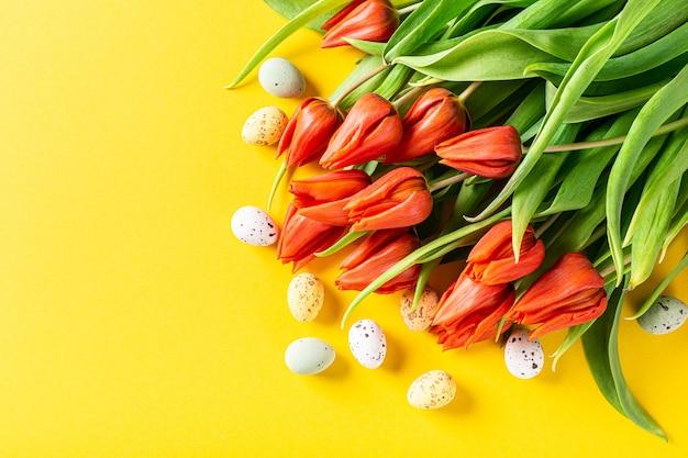 Tulipani arancioni e uova di quaglia sulla superficie gialla, pasqua. compleanno, concetto di cartolina d'auguri festa della mamma con lo spazio della copia. vista dall'alto, piatto
