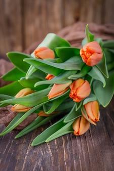 Tulipani arancioni su un fondo rustico in legno