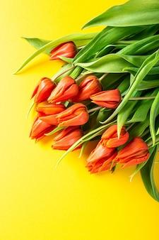 Tulipani arancioni sulla superficie gialla, pasqua. compleanno, concetto di cartolina d'auguri festa della mamma con lo spazio della copia. vista dall'alto, piatto