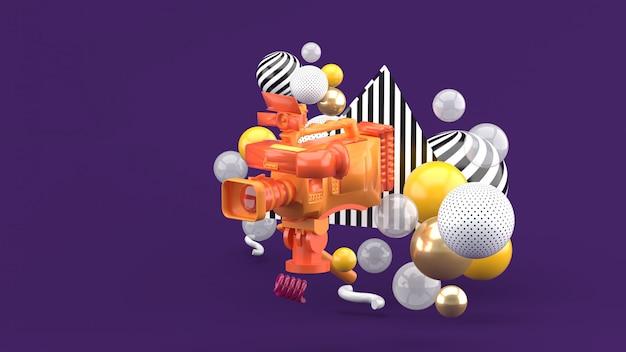 Una videocamera arancione circondata da palline colorate su viola. rendering 3d