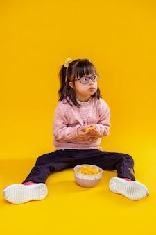 Sulla parete arancione. curiosa piccola signora seria seduta sul pavimento nudo contro la ciotola piena di spuntini malsani