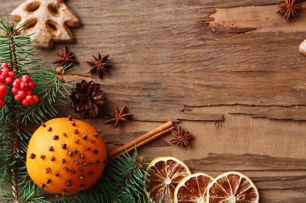 Arancia con biscotti, spezie, fette di limone essiccato e rametti di albero di natale su fondo di legno rustico