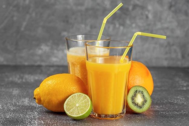 Un'arancia avvolta con un metro a nastro e una pinza circondata da frutta fresca e bicchieri di succo e frullati. il concetto di dimagrimento, porta la figura in forma.