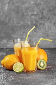 Un'arancia avvolta con un nastro di misurazione e una pinza circondata da frutta fresca e bicchieri di succo e frullati su uno sfondo grigio cemento. il concetto di dimagrimento, porta la figura in forma.