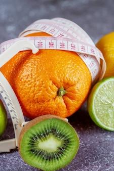 Un'arancia avvolta con un nastro di misurazione e una pinza circondata da frutta fresca su uno sfondo grigio cemento. il concetto di dimagrimento, rimuovere la cellulite, dare forma alla figura.