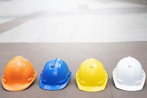 Cappello del casco di usura di sicurezza duro arancione, giallo, blu e bianco nel progetto al cantiere edile sul pavimento di cemento sulla città