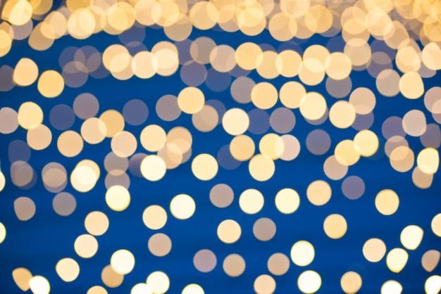 Le luci natalizie sfocate arancioni e gialle possono essere utilizzate per lo sfondo