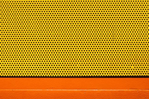 Placca di metallo di colore giallo arancio con molti piccoli fori circolari punteggia la struttura per fondo