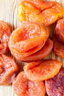 Albicocche secche arancioni e gialle su un tavolo di legno