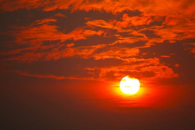 Cielo rosso giallo arancione della siluetta nel tramonto indietro sulla nuvola
