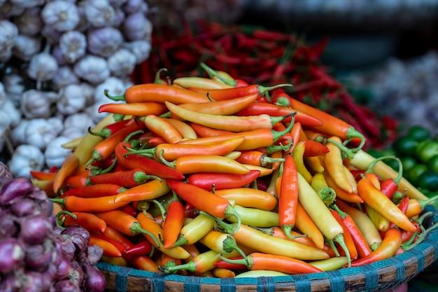 Peperoni arancioni, gialli e rossi in vendita al mercato alimentare di strada nella città vecchia di hanoi, vietnam. avvicinamento