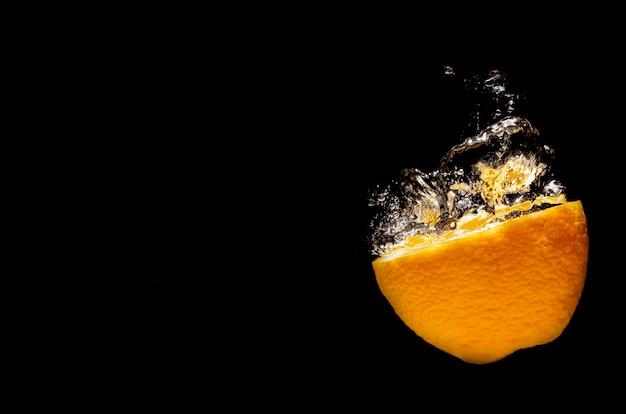 Arance che cadono in spruzzi d'acqua su sfondo nero e fanno bene alla salute.