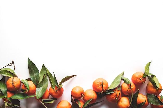 Composizione di frutti di arance con foglie verdi su fondo di legno bianco, vista dall'alto