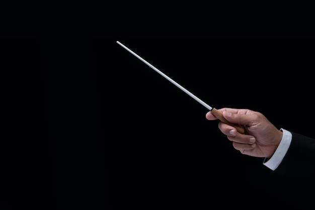 Il direttore d'orchestra passa il testimone. mani del conduttore tenendo il bastone su uno sfondo nero.