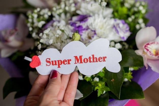 Fiori di orchidea e regalo floreale per la mamma. il concetto di felice festa della mamma. messaggio in mano femminile, super mamma. foglio bianco con cuore rosso e testo super mamma.