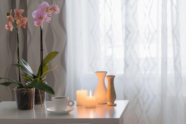 Orchidee, tazza, candele sul tavolo nella stanza