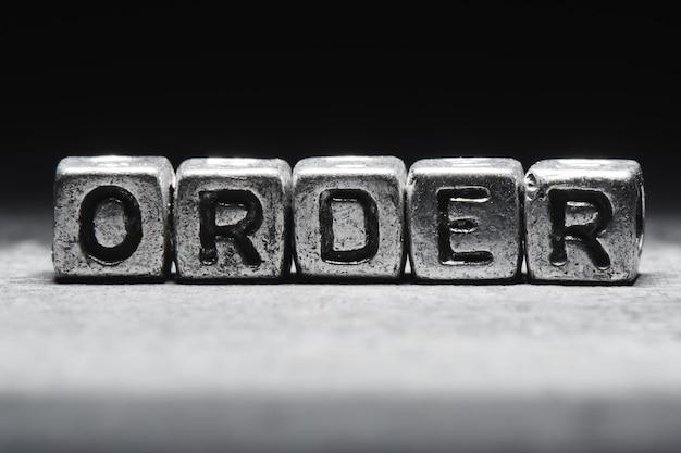 Concetto di ordine. iscrizione 3d su cubi di metallo su sfondo nero grigio isolato