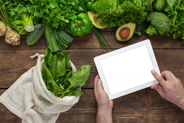 Ordina cibo online l'uomo tiene il tablet con schermo vuoto per il tuo messaggio di testo o disegno sul tavolo di legno con verdure verdi fresche e borsa in tessuto