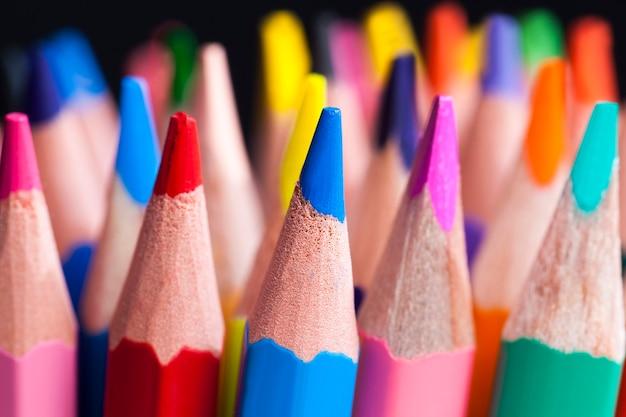 Matita in legno colorata ordinaria con mina morbida di diversi colori per il disegno e la creatività, primo piano delle matite dopo l'affilatura e l'uso, matita realizzata con materiali naturali sicuri per i bambini