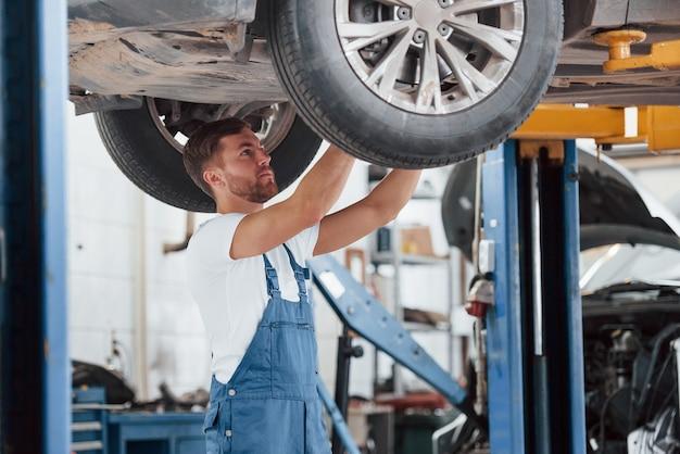 Giornata ordinaria del meccanico. l'impiegato con l'uniforme di colore blu lavora nel salone dell'automobile.