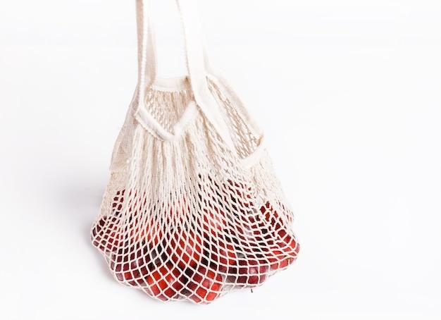 Mele biologiche in borsa di vimini per lo shopping su sfondo bianco, concetto di borsa della spesa eco. concetto zero rifiuti con spazio copia, concetto senza plastica