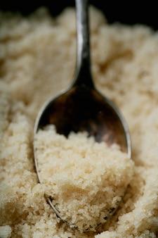 Zucchero di canna biologico in un cucchiaio. avvicinamento