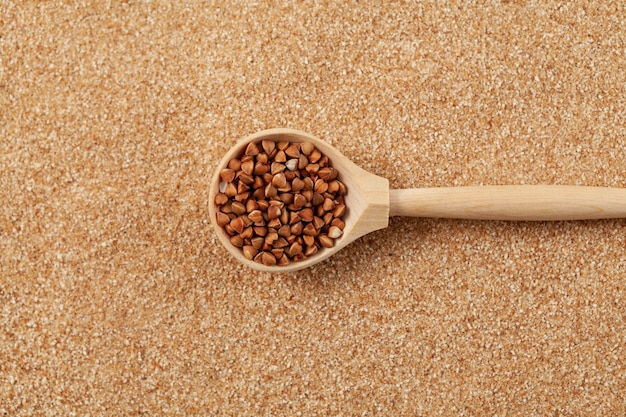 Grano saraceno organico in cucchiaio di legno su fondo di farina di grano saraceno macinata o scaglie