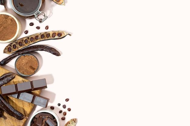 Baccelli di carruba organici, polvere e melassa di carruba su fondo beige, cibo sano di carrube, ceratonia siliqua harnup. alimentazione vegana naturale. sfondo di cibo creativo. copia spazio. piatto lay.vista dall'alto