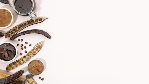 Polvere organica dei baccelli di carruba e melassa di carruba su un alimento sano di carrube di fondo beige