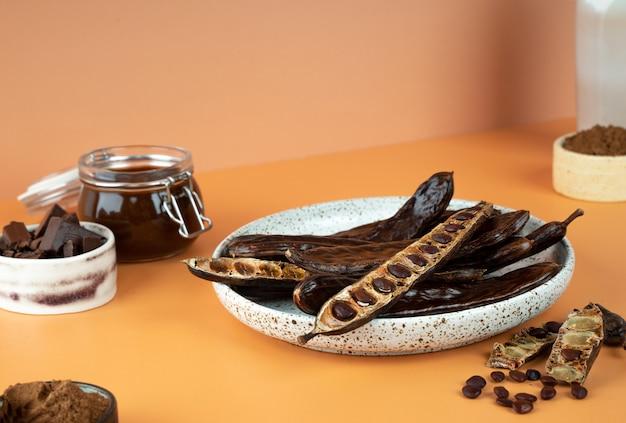 Semi organici dei baccelli di carruba in un piatto di ceramica su un fondo beige di carrube cibo sano ceratonia