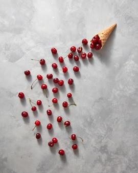 Le ciliegie organiche vengono versate da un corno di cialda su uno sfondo di pietra grigia con spazio di copia. disposizione piatta. concetto estivo di gelato artigianale