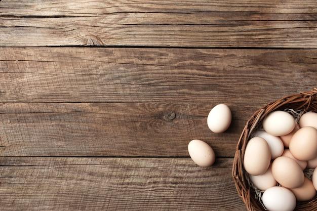 Uova di gallina organiche in cestino su fondo di legno. concetto di famiglia biologica con uova di galline allevate a terra e al pascolo