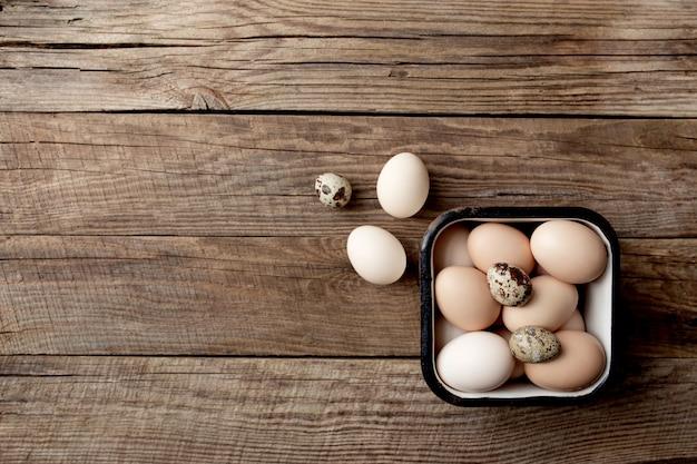 Pollo organico e uova di quaglia in scatola di metallo su fondo di legno. concetto di famiglia biologica con uova di galline allevate a terra e al pascolo