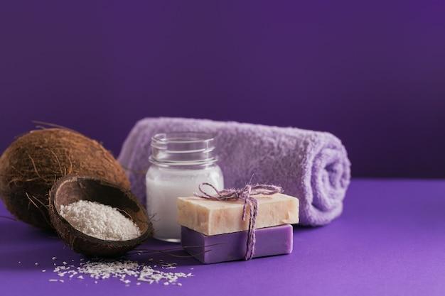Olio cosmetico di cocco biologico e sapone naturale fatto a mano con cocco e fiocchi di cocco sul colore viola