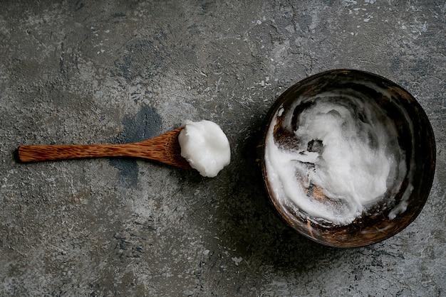 Olio di cocco biologico in ciotola di cocco con cucchiaio di cocco. concetto di sostenibilità. vista dall'alto. lay piatto.