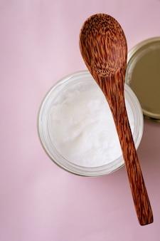Olio di cocco biologico nel barattolo di vetro con cucchiaio di cocco. concetto di sostenibilità. vista dall'alto. lay piatto.