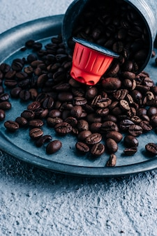 Capsula di caffè biologica con chicchi di caffè su sfondo colorato. contrasto di colore. copia spazio