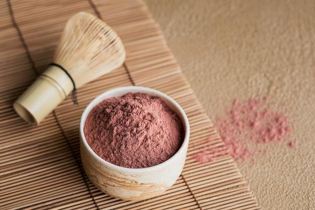 Tè in polvere di colore organico matcha con frusta di bambù di strumenti giapponesi su sfondo beige. concept bevanda salutare vegetariana, bevanda