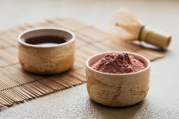 Tè matcha in polvere di colore biologico con frusta di bambù di strumenti giapponesi su superficie beige