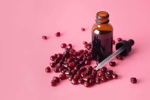 Olio di semi di melograno cosmetico biologico in flacone contagocce marrone sulla superficie rosa.