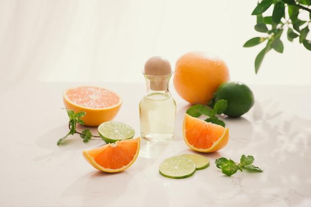 Cosmetici biologici con estratti di erbe di limone, arancia, menta su sfondo luminoso