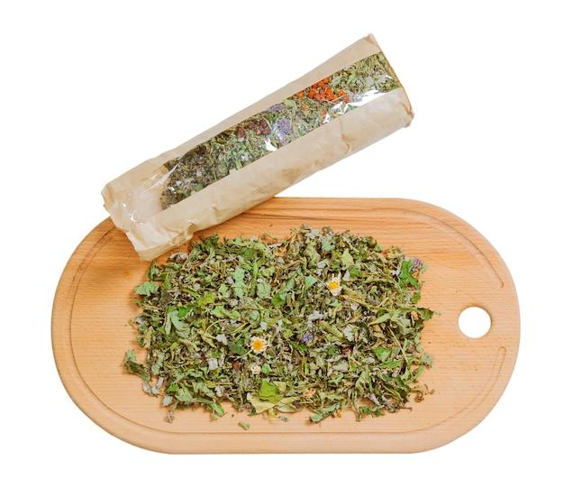 Tè alle erbe essiccato biologico con confezione su tagliere da cucina in legno su sfondo bianco