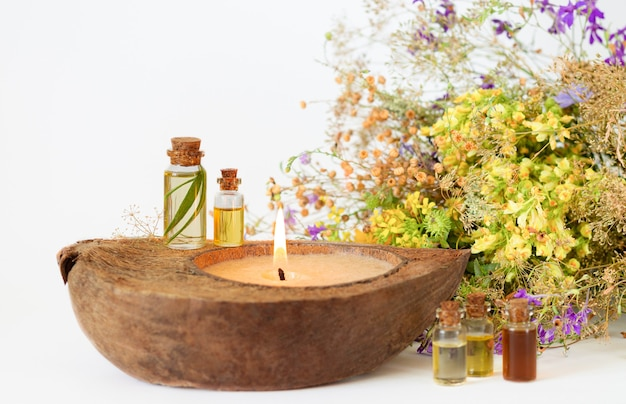 Oli aromatici essenziali biologici in bottiglie di vetro, erbe medicinali e candela ecologica. messa a fuoco selettiva