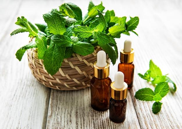 Olio essenziale biologico di menta con foglie verdi su fondo di legno bianco