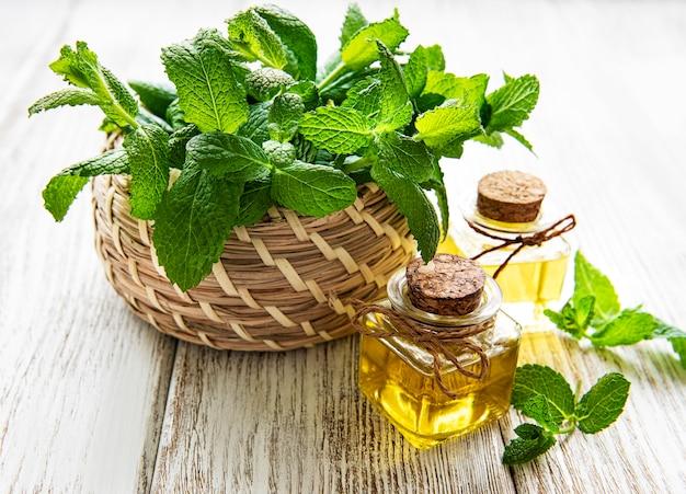 Olio essenziale biologico di menta con foglie verdi su un legno bianco