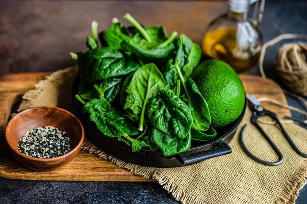 Concetto di cibo biologico con foglie fresche di spinaci baby e avocado