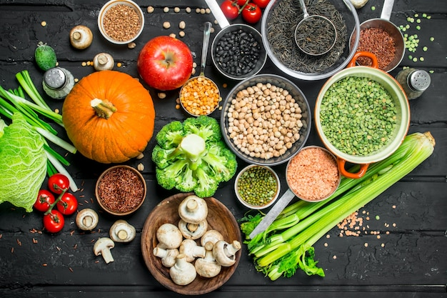 Cibo organico. diversa gamma di frutta e verdura con legumi su un tavolo rustico nero.