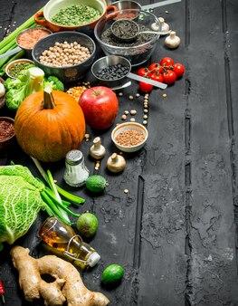 Cibo organico. diversa gamma di frutta e verdura con legumi. su un tavolo rustico nero.