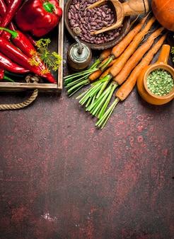Cibo organico. raccolto fresco di legumi e ortaggi. su fondo rustico.